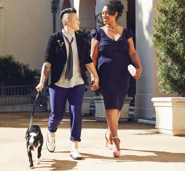 Hand-in-hand, newlyweds walking their dog.